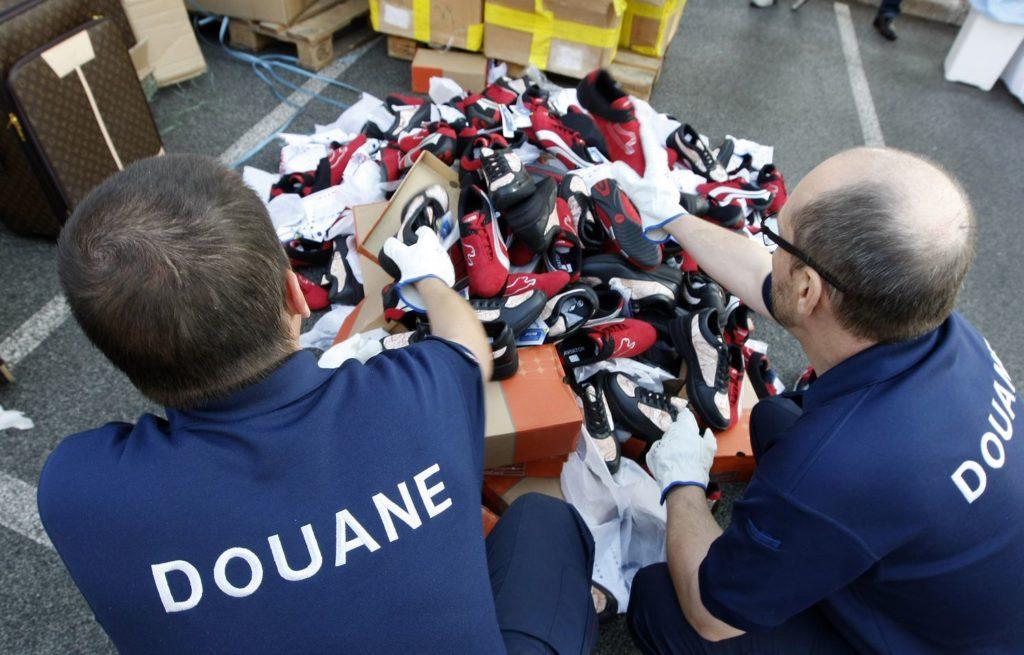 Douaniers français montrant des chaussures contrefaites avant qu'elles ne soient détruites.